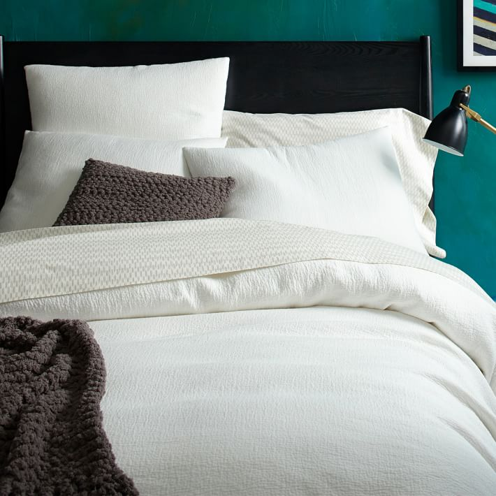 White-bedding-pops-against-a-teal-wall