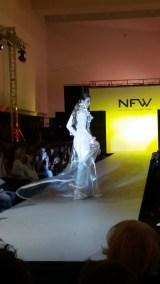 Vista trasera de chubasquero de plástico con detalles bordados y vestido de pedrería. ALICIA ARZA.