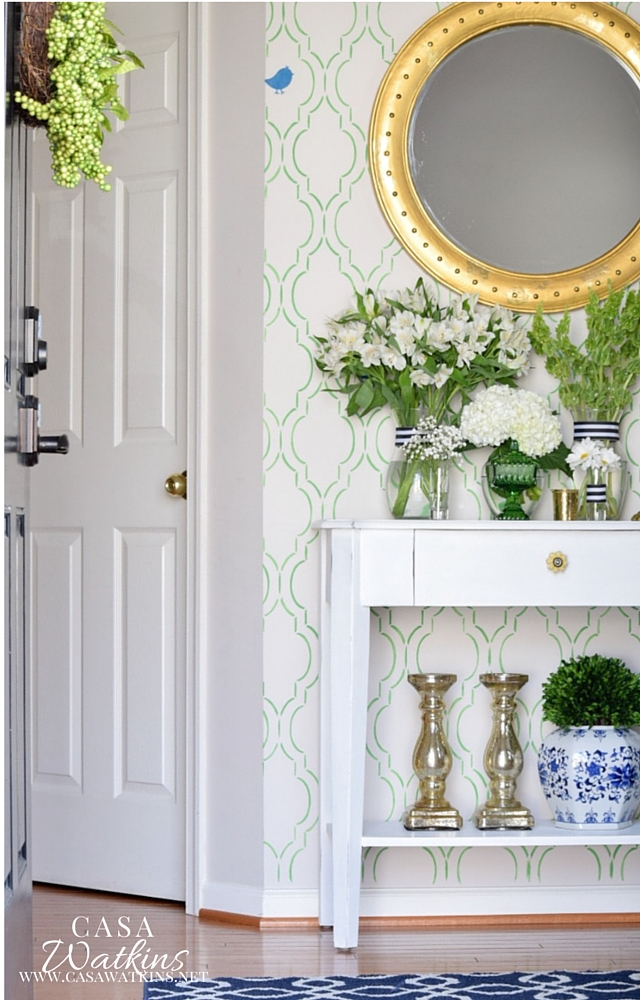 Green and white entryway with gold touches and chinoiserie blue jars
