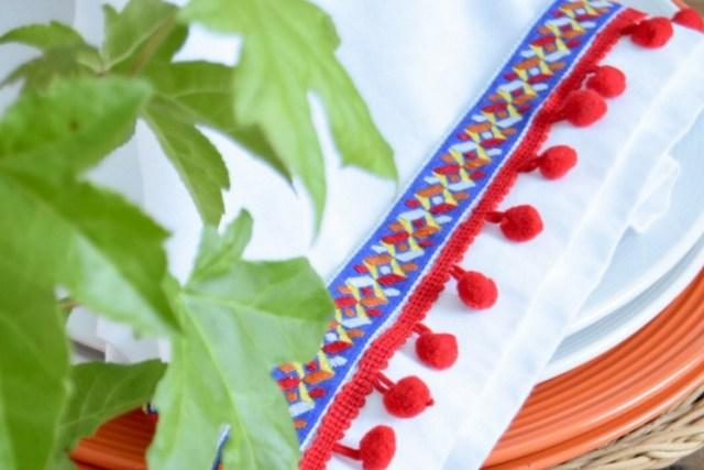 DIY red pom pom napkins with colorful trim