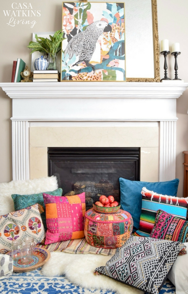 Colorful boho pillows on floor with layered rugs around the fireplace