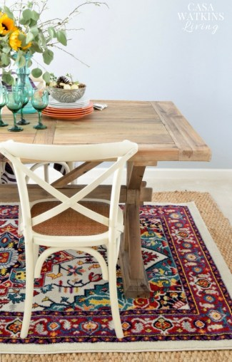 Love this colorful rug in this global eclectic dining room!