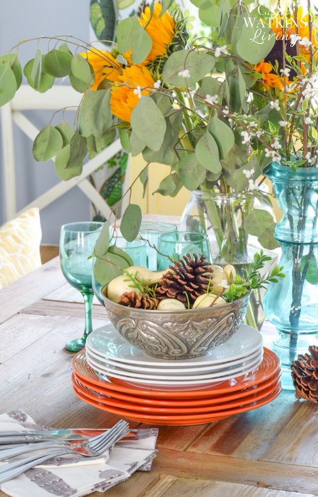 fall centerpiece with sunflowers, silver bowl display, and stacked plates