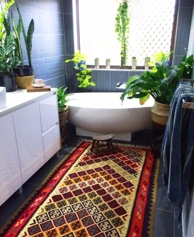 Stunning boho bathroom with dark tile and kilim rug by La Boheme House