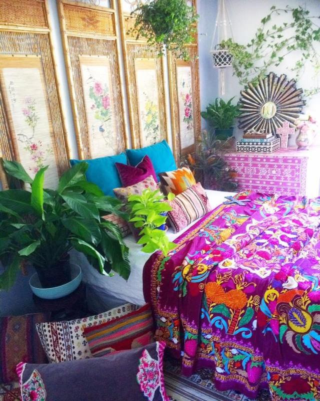 Colorful boho bedroom with suzani blanket, bone inlay chest, and plants from La Boheme House