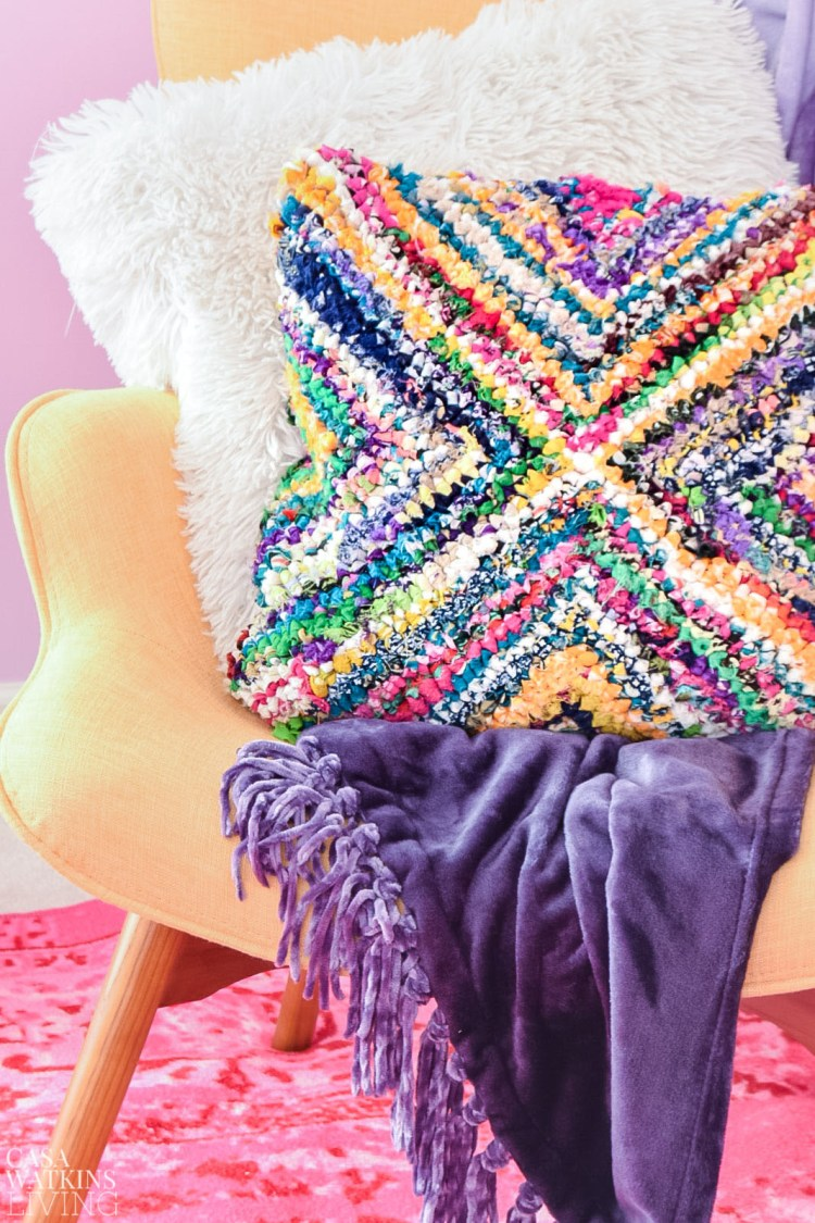 colorful yellow midcentury modern chair with purple velvet blanket