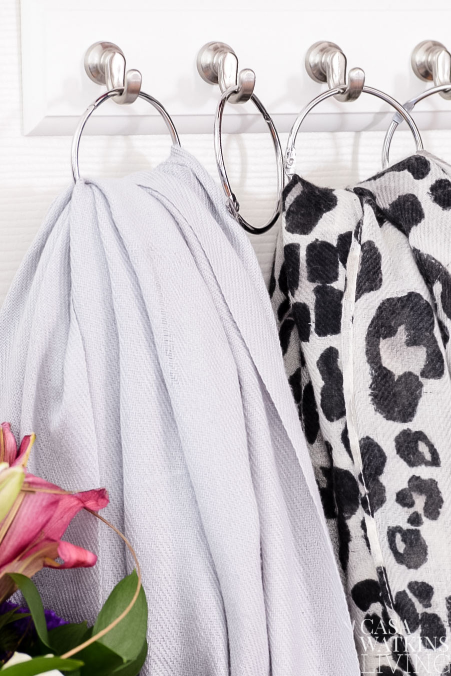 Use shower curtain rings on a hook for scarf organization in a coat closet
