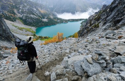 Backpacker viewing Colchuck Lake from Aasgard Pass, The Enchantments, Alpine Lakes Wilderness, Washington.