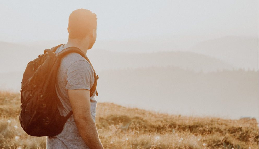 Man staring off into the distance over some hills