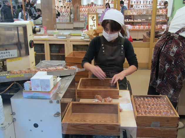 A woman hard at work packaging the thousands of momiji-manju that will be sold in her shop on Miyajima.
