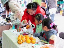 Kids watch as their mother explains how to puncture the orange to insert the cloves