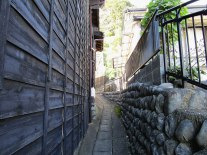 A narrow walkway between buildings leading to the trail up to Satta Pass