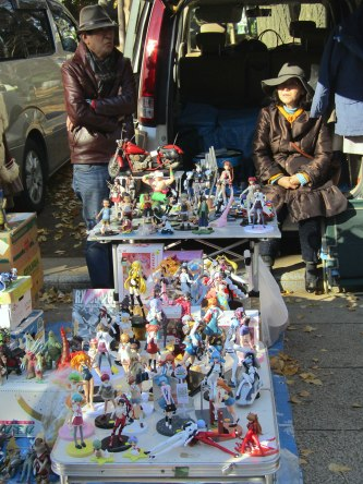 A couple wait patiently for someone to check out their collection of anime character action figures