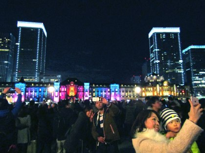 Visitors posing for selfies in front of Tokyo Station's Marunouchi Building illuminations