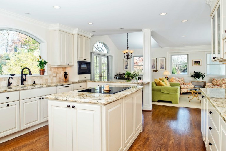 bright kitchen with island and peninsula flows into living area french doors