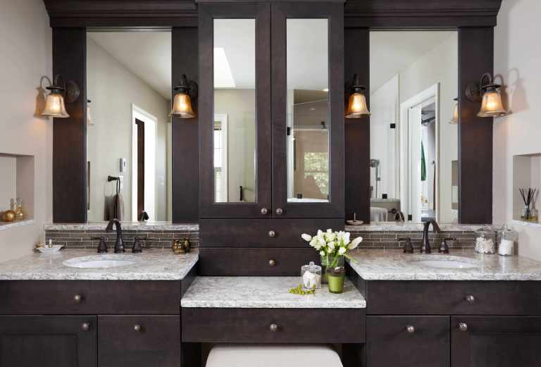 dark wood vanity with double sinks and built in makeup area plenty of storage sconce light