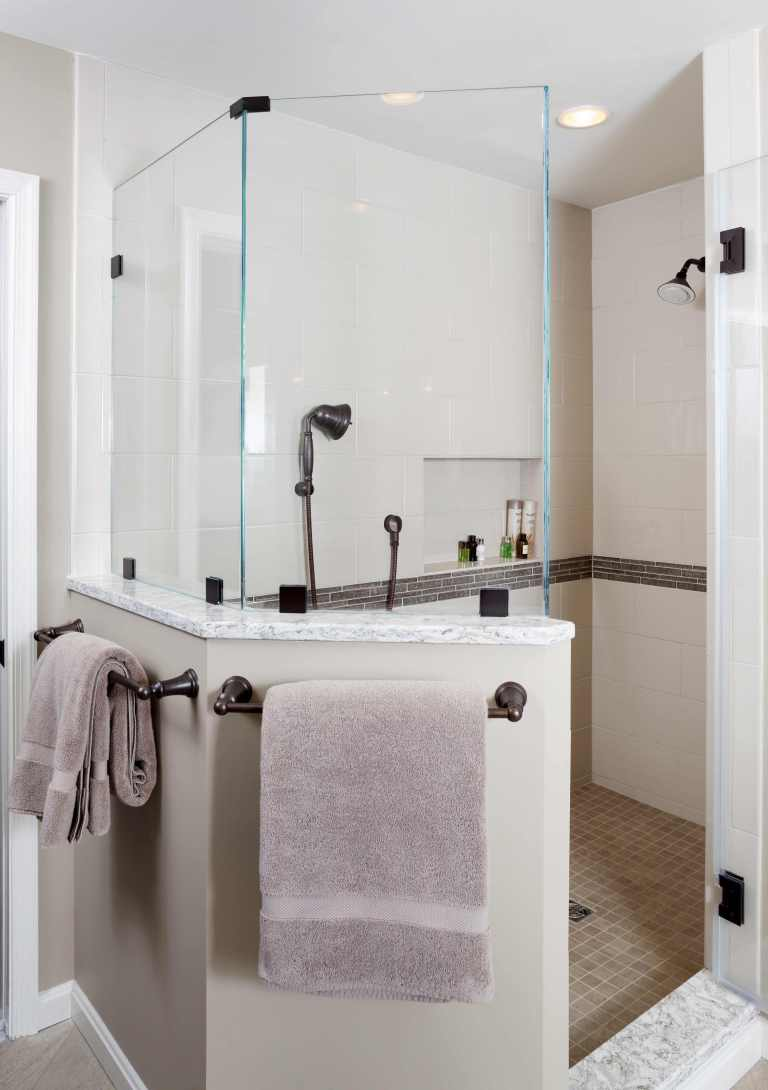 separate shower stall half wall with glass built in storage nook and tile stripe detail neutral color palette