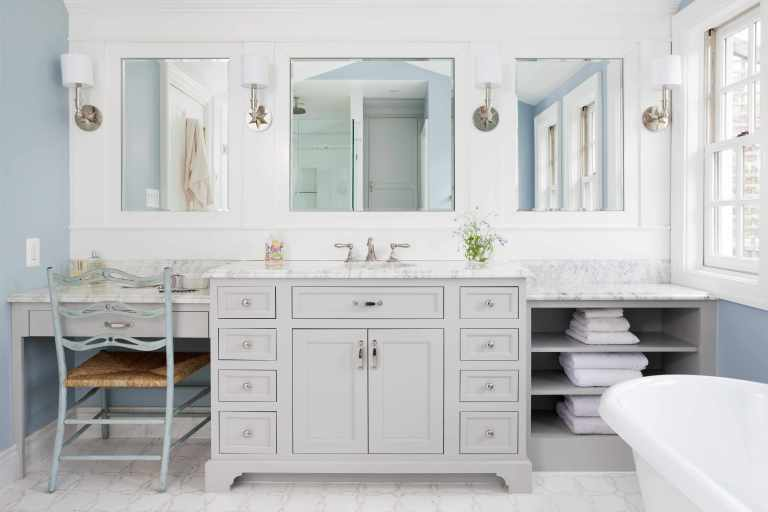 large vanity with sink and built in makeup area gray cabinetry open shelving storage soft neutral color palette sconce lighting