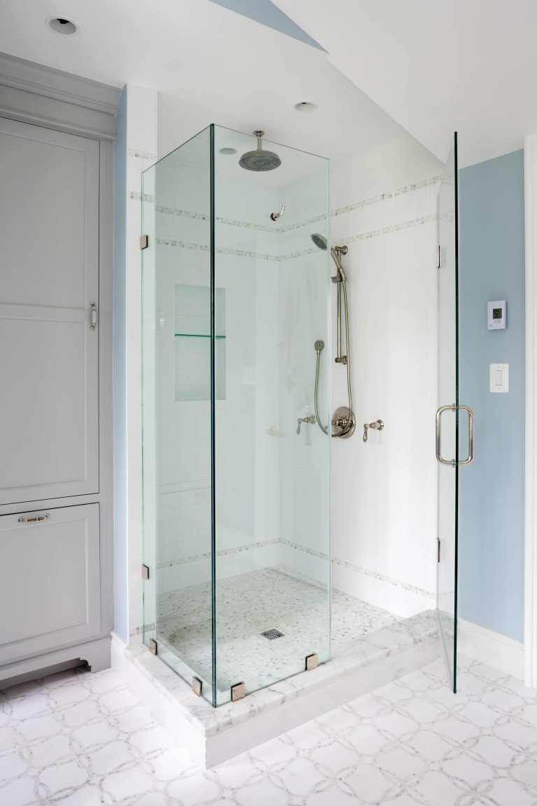 separate shower stall with glass wall and built in storage nook