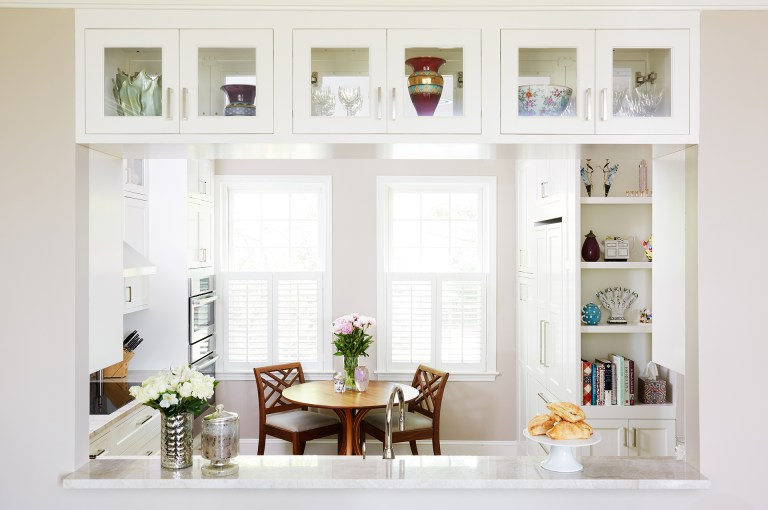 bright white kitchen passthrough into dining area with upper glass door cabinetry