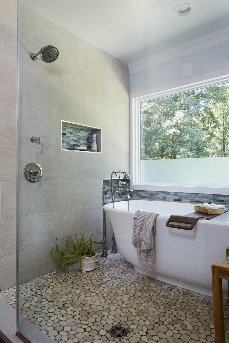 shower area with big window and glass wall freestanding tub storage nooks with accent tile pebble tile floor