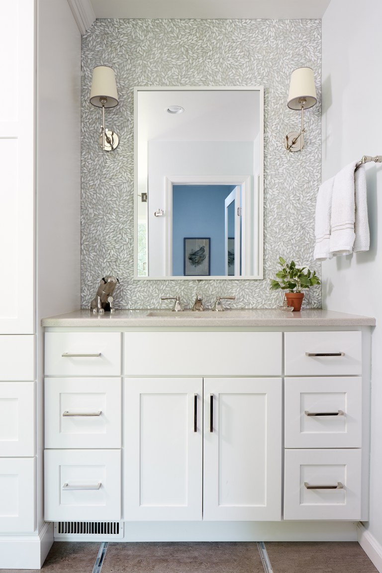 bathroom vanity white cabinetry tile feature wall behind mirror and sconce lighting
