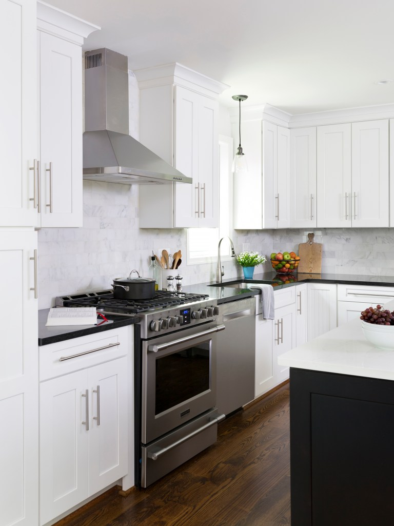 stainless steel gas range and hood white cabinetry black countertops