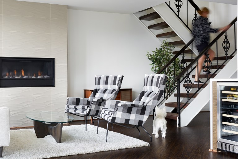 living room with textured fireplace surround and open staircase