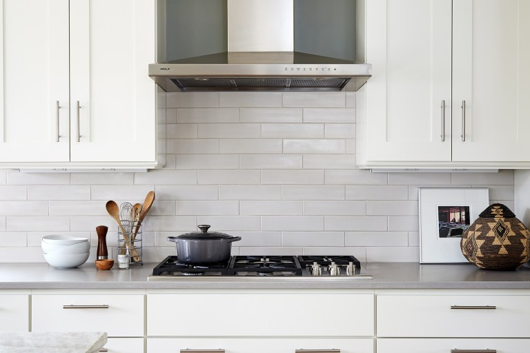 gas stovetop and stainless steel range hood white subway tile backsplash
