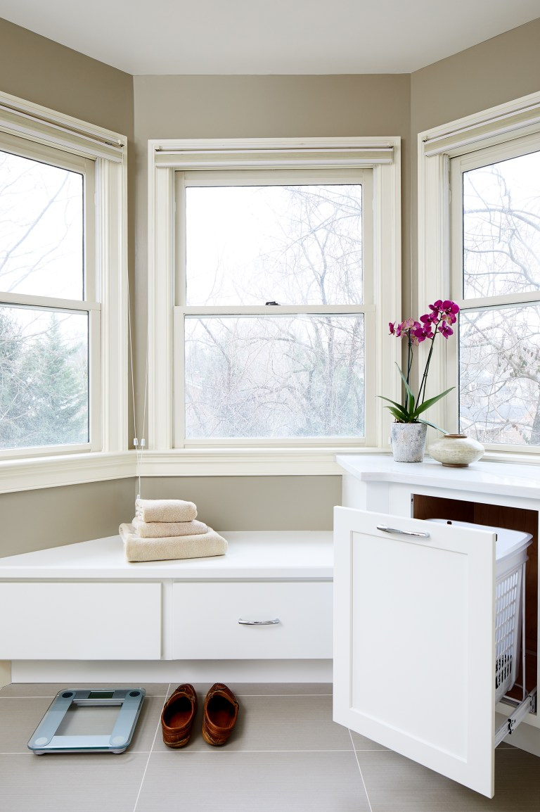 built in storage bench under windows and cabinetry to hide laundry hampers