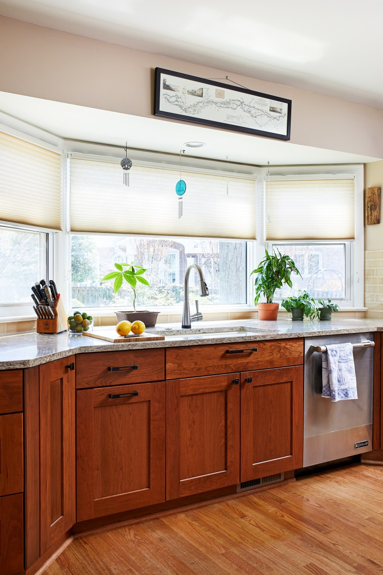 kitchen sink in front of large bay window medium stained cabinetry and wood floors