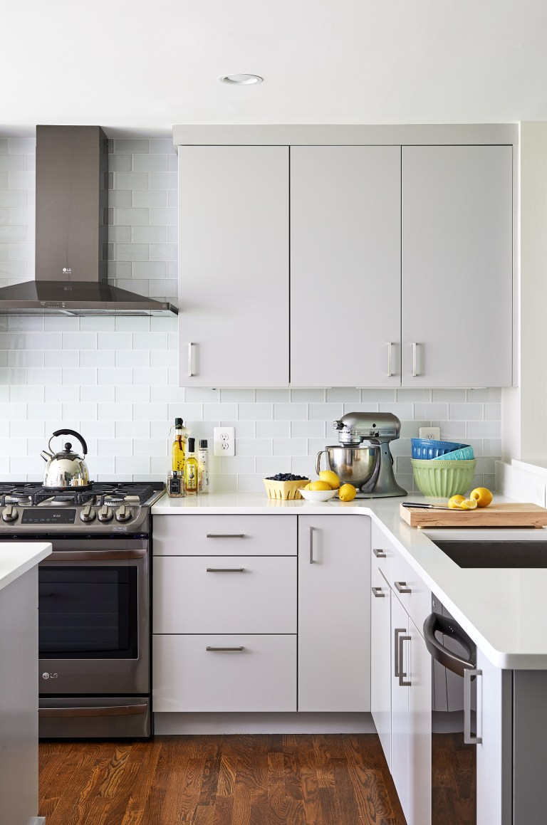 white and gray modern kitchen sleek cabinetry glass tile dark stainless steel appliances