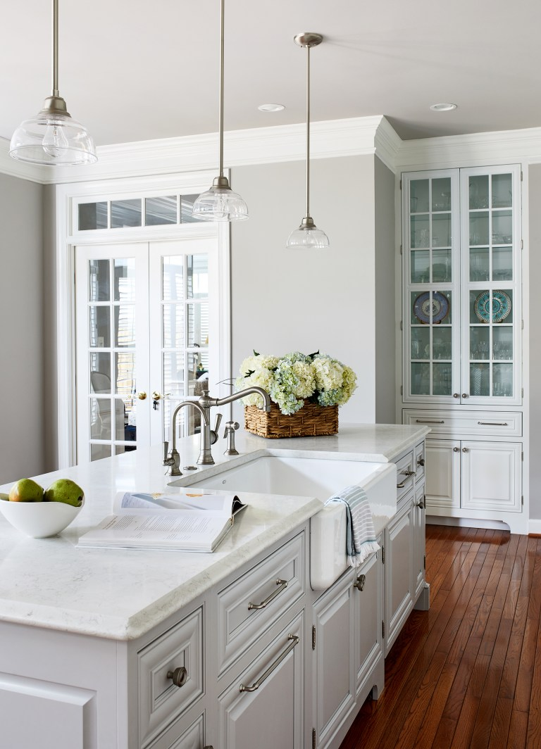 traditional kitchen with 3- hanging light pendants over kitchen island, large white farmhouse sink, hardwood floors