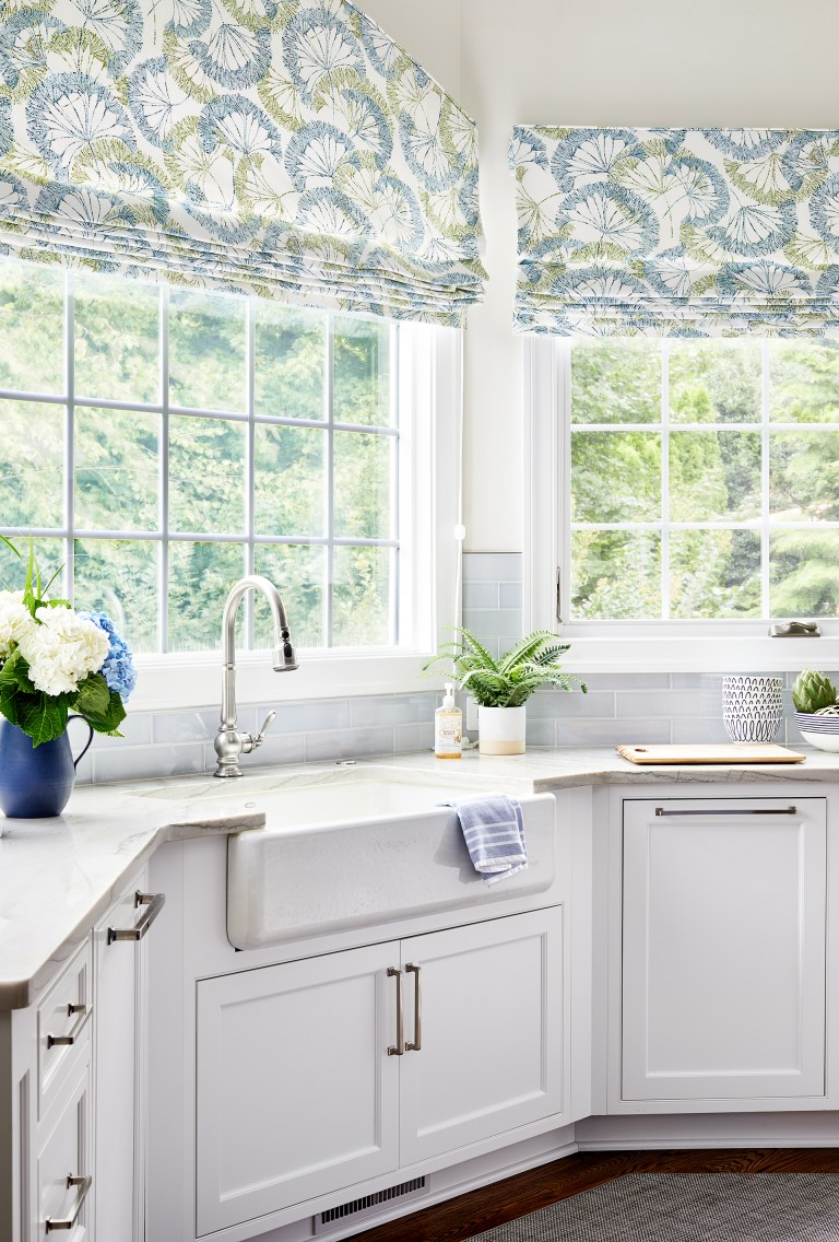 kitchen bay window with white farmhouse sink and blue, yellow white shades