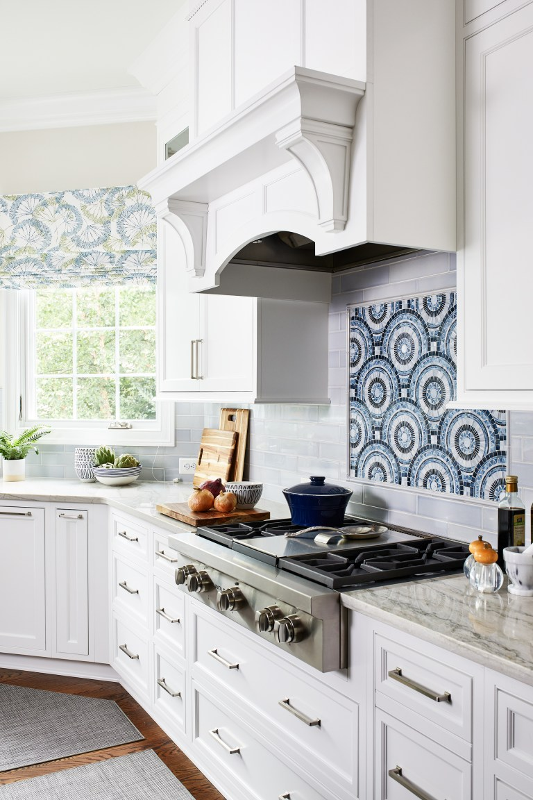 kitchen white panel hood by large window paired with marble countertop and under cooktop drawers with pull handles
