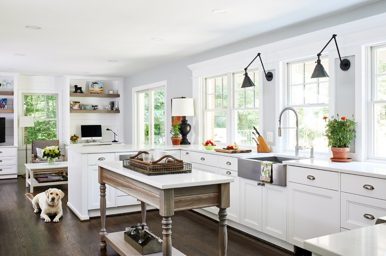 maryland home renovation kitchen with two lamps wall light fixtures with farmhouse apron sink, band of windows over farmhouse sink with polished nickel gooseneck faucet mounted above white cabinets and drawers with pull handles.