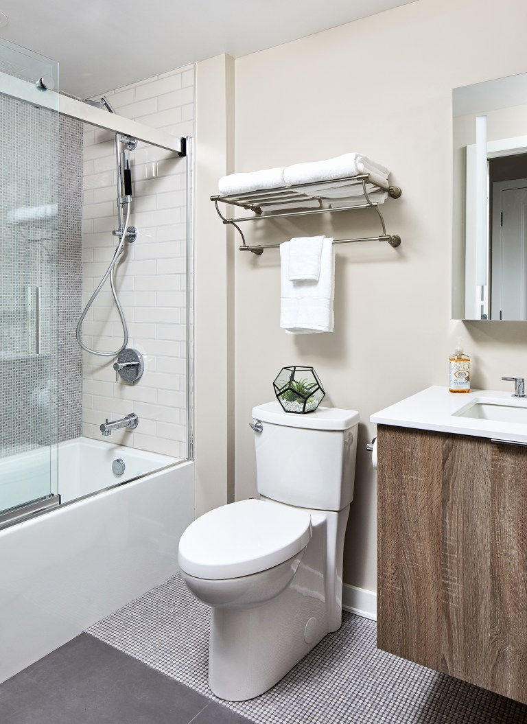 Bathroom with above the toilet storage shelf with single sink and rectangular mirror