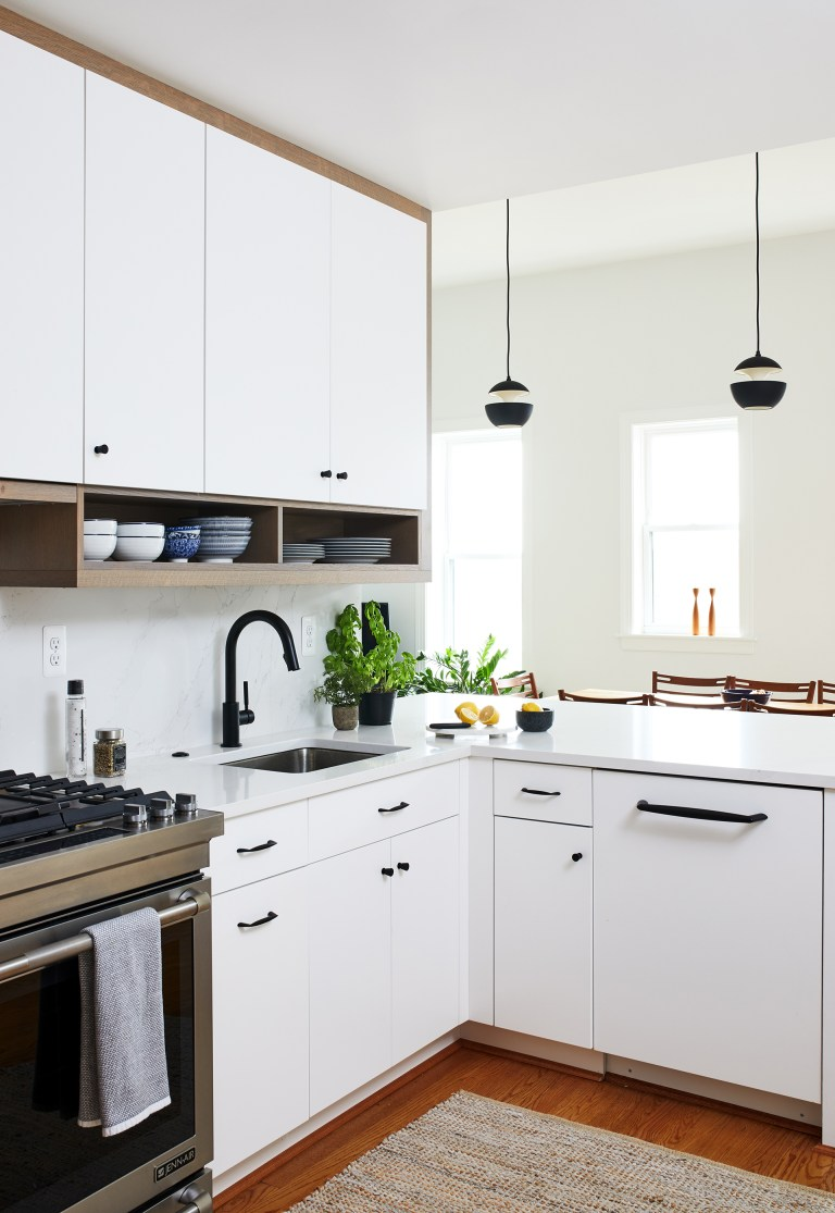 White cabinets with black handles and knobs with a black faucet