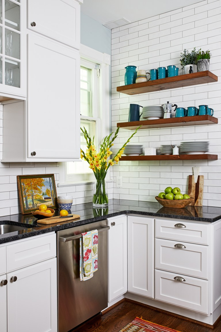 case design kitchen with black counter top with white cabinets, small corner window