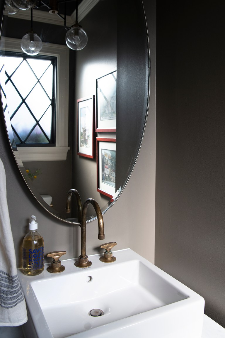 traditional bathroom with large oval mirror above single sink