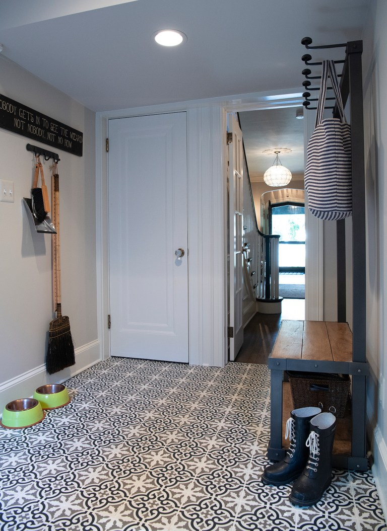 white and black tiles with wooden hallway bench
