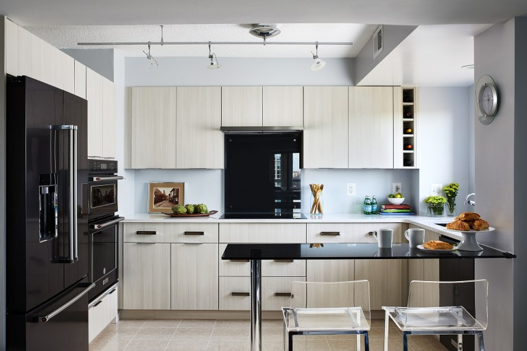 Black appliance with white cabinets and black wall mounted kitchen table with two sits