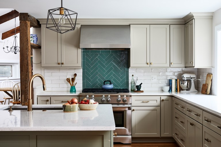 Kitchen lighting above kitchen island with a green backsplash and white cabinets