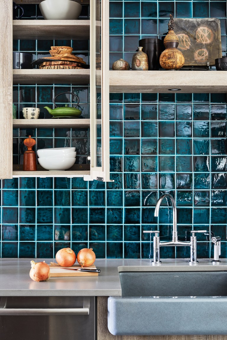 close up of sink with teal tile backsplash and glass door cabinetry and open shelving