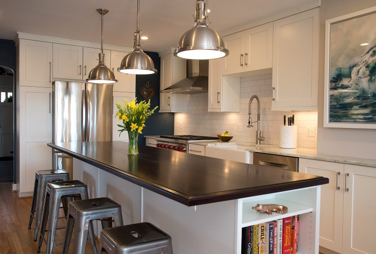 seating at kitchen island with black countertops and open side storage pendant lighting