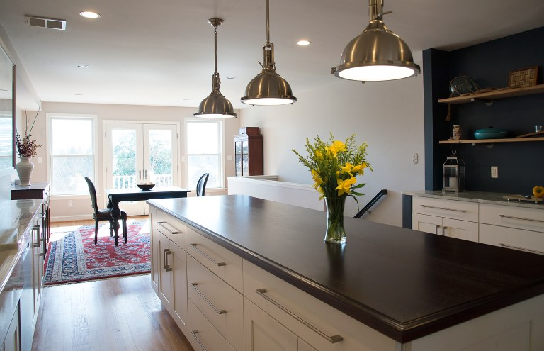 kitchen island with black countertops and open side storage pendant lighting