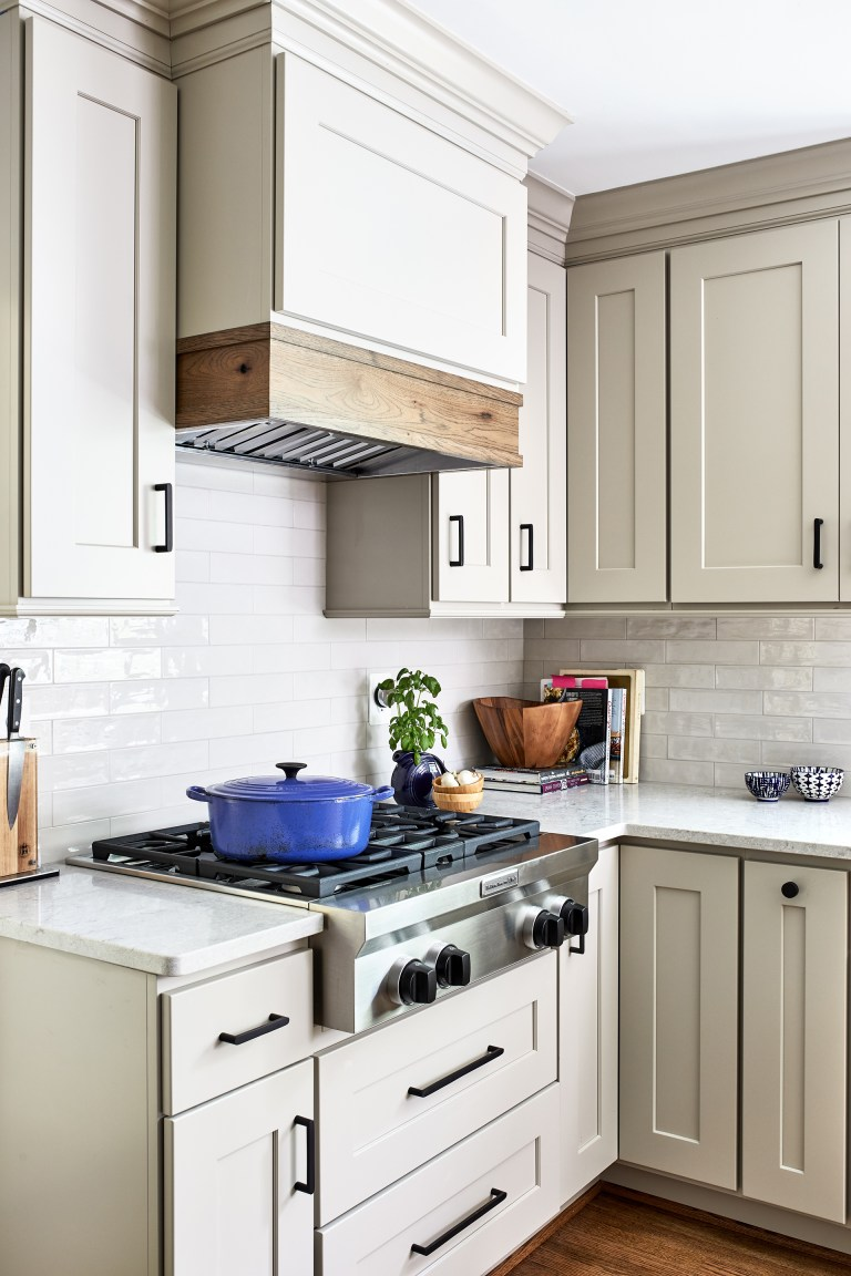 white cabinets with black pull handles, stove top 4 burners and wood hood range
