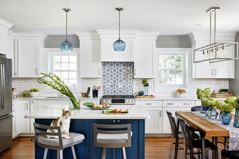 large kitchen remodeling in Virginia with white marble countertop and blue cabinets underneath kitchen island with blue glass shade light fixtures above and wooden 6 chairs table with pendant with 5 light kitchen linear pendant above.