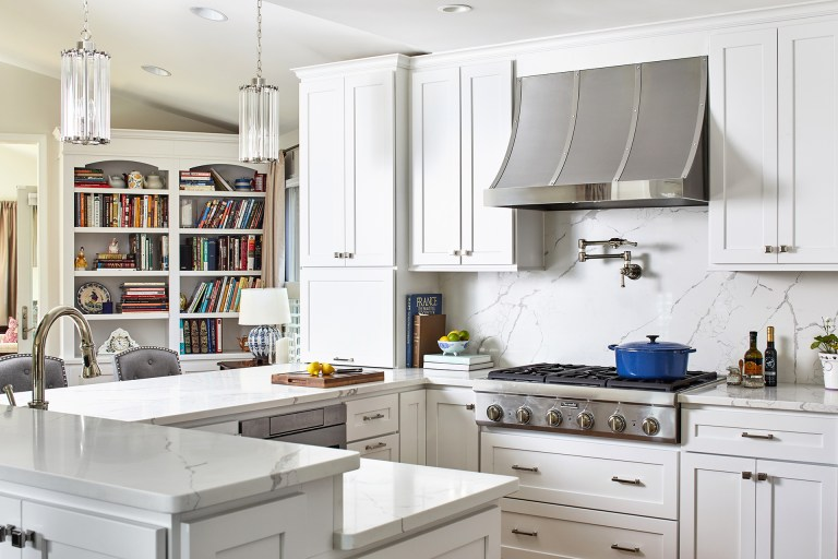 case kitchen design with white marble countertops, white marble backsplash with tall white cabinets with pull handles