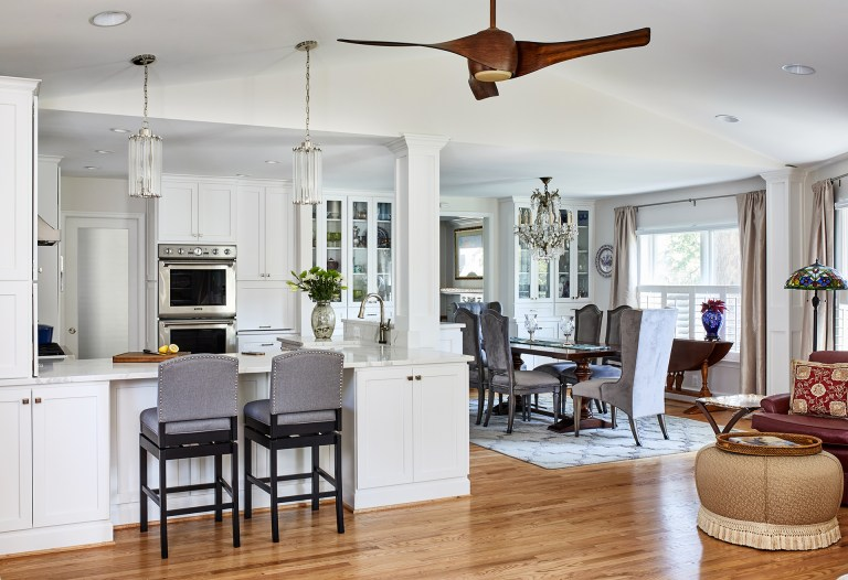 transitional style open kitchen open to the dining room and living room, wooded flooring high vaulted ceiling with a wooded ceiling fan